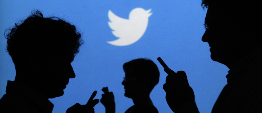 People holding mobile phones are silhouetted against a backdrop projected with the Twitter logo in this illustration picture taken in  Warsaw September 27, 2013. Twitter Inc, the eight-year-old online messaging service, gave potential investors their first glance at its financials on Thursday when it publicly filed its IPO documents, setting the stage for one of the most-anticipated debuts in over a year. Picture taken September 27.  REUTERS/Kacper Pempel (POLAND - Tags: BUSINESS TELECOMS LOGO) - BM2E9A410KY01