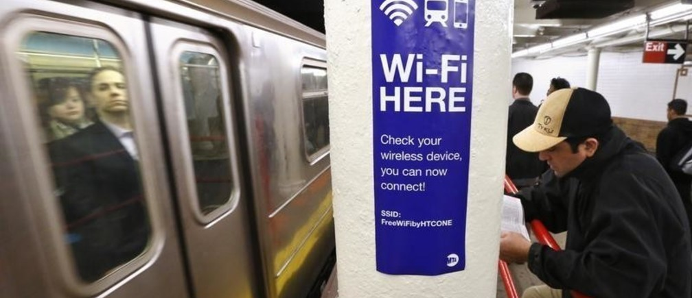 A sign advertises Wi-Fi service in the Times Square Subway station in New York, April 25, 2013. The New York MTA has expanded service to 30 additional stations, including Times Square, Rockefeller Center and Columbus Circle. AT&T and T-Mobile signed 10-year contracts to provide cell and Wi-Fi service through a network being built by Transit Wireless. REUTERS/Brendan McDermid (UNITED STATES - Tags: SCIENCE TECHNOLOGY BUSINESS TELECOMS TRANSPORT) - GM1E94Q00J301