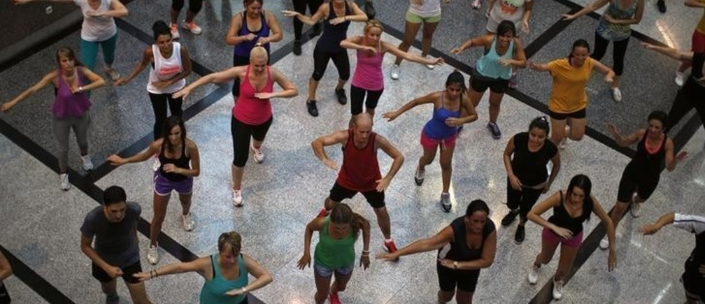 People take part in an aerobics class at a shopping centre in Malaga, southern Spain, August 1, 2014. Picture taken August 1, 2014. REUTERS/Jon Nazca (SPAIN - Tags: HEALTH SOCIETY)