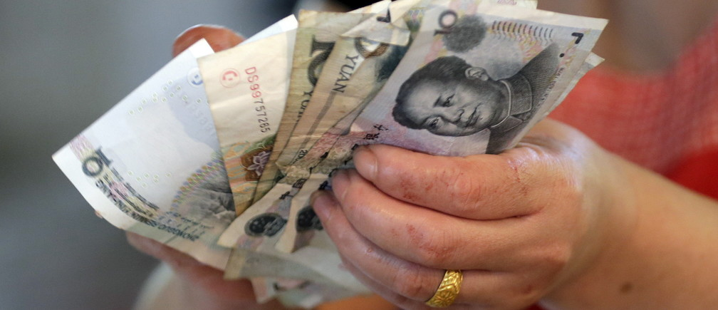 A vendor holds Chinese Yuan notes at a market in Beijing, August 12, 2015. China shocked global markets on Tuesday by devaluing its currency after a run of poor economic data, a move it billed as a free-market reform but which some experts suspect could be the beginning of a longer-term slide in the exchange rate. REUTERS/Jason Lee  - GF20000020395