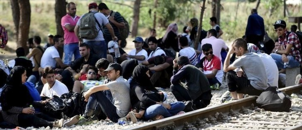 Migrants wait on the Greek side of the border to enter Macedonia near Gevgelija, Macedonia, en route to northern Europe, July 20, 2015. The European Union failed to reach a deal to resolve a migration crisis in the Mediterranean, and instead set a deadline of July 20 to reach an agreement on how to redistribute 40,000 asylum seekers currently in Italy and Greece. REUTERS/Ognen Teofilovski