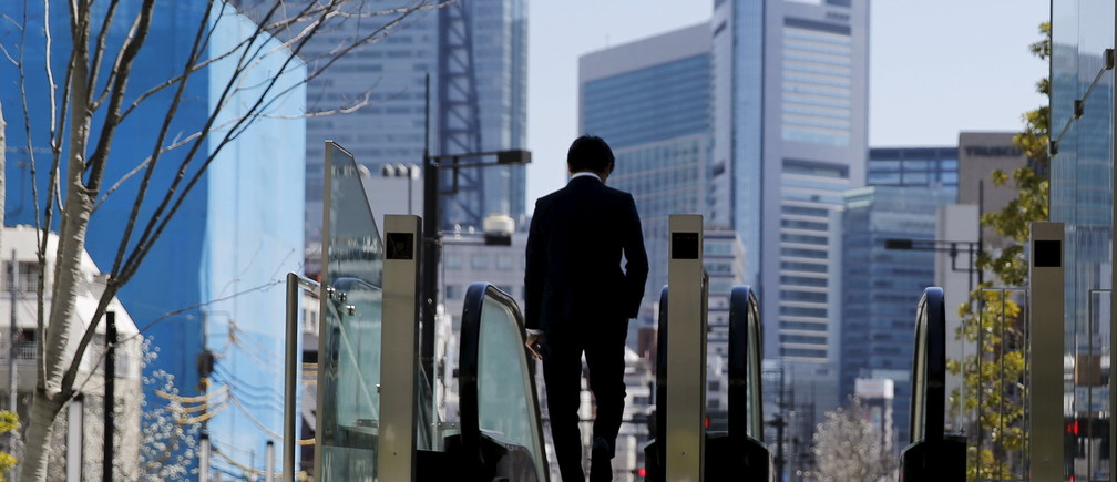 A businessman rides an escalator outside a commercial building in Tokyo March 26, 2015.