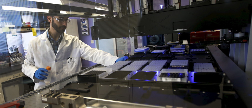 Technician Matthew Smith loads a robotic DNA sample automation machine at a Regeneron Pharmaceuticals Inc. laboratory at the biotechnology company's headquarters in Tarrytown, New York March 24, 2015.