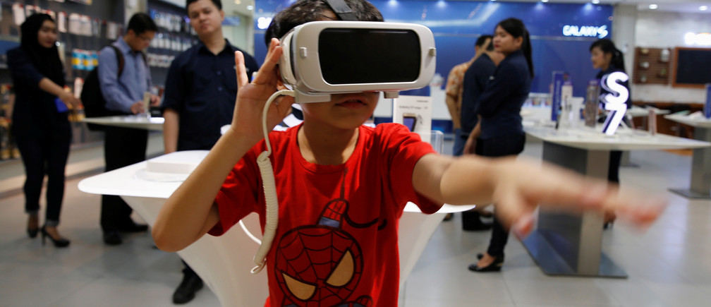 A child reacts as he uses the Samsung Gear VR at a Samsung showroom in Jakarta, Indonesia, May 26, 2016.