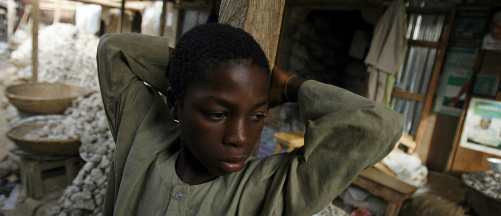 A boy rests in front of shops in the old market of Kano April 24, 2007. Many working children in towns are engaged in different activities like street traders or apprentices to artisans and most start working between the ages of five and nine and continued into adulthood.