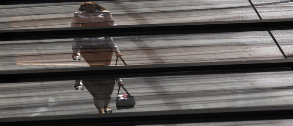 An office worker with a shopping bag is reflected on the roof of a building in central Sydney February 5, 2013. Picture rotated 180 degrees. Australia's central bank kept its main cash rate steady at a record-matching low of 3.0 percent on Tuesday, a widely expected decision given how the global background had brightened since its last easing in December. REUTERS/Daniel Munoz (AUSTRALIA - Tags: BUSINESS TPX IMAGES OF THE DAY) - GM1E9250X6201