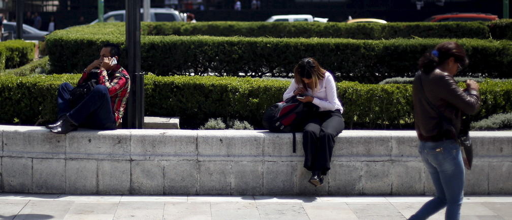 People use their cell phones in Mexico City, October 8, 2015.