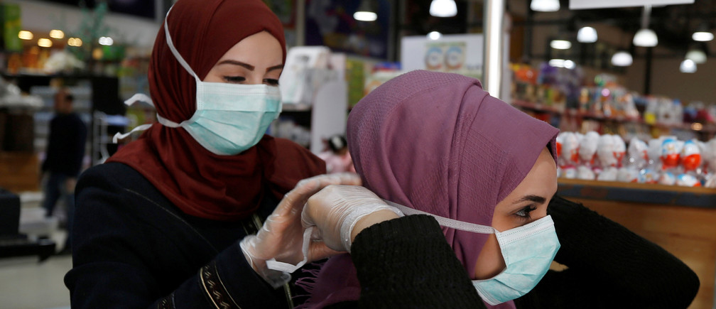 A Palestinian cashier is helped by her colleague to wear a mask amid coronavirus precautions, in a supermarket in Gaza City March 8, 2020. Picture taken March 8, 2020. REUTERS/Mohammed Salem - RC2EGF9WAML5