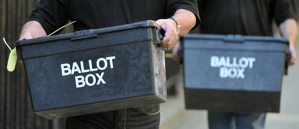 Members of an electoral services team deliver ballot boxes to a polling station in London May 4, 2011. Britons appeared set to reject electoral reform in a referendum that has divided the year-old coalition government and raised doubts about its durability.   REUTERS/Toby Melville (BRITAIN - Tags: ELECTIONS POLITICS) - LM1E7540VQL01