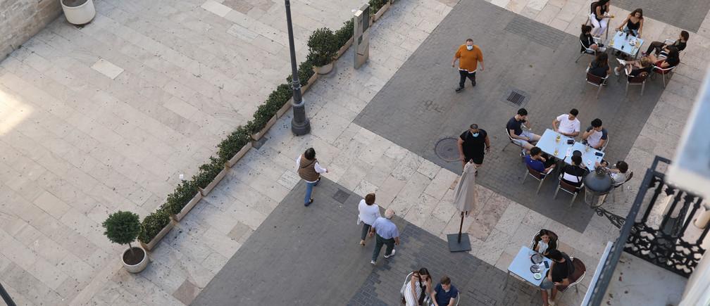 La gente se sienta en la terraza de un bar, ya que en algunas provincias españolas se permite relajar las restricciones de cierre durante la primera fase, en medio del brote de la enfermedad coronavirus (COVID-19), en Valencia, España, el 18 de mayo de 2020.