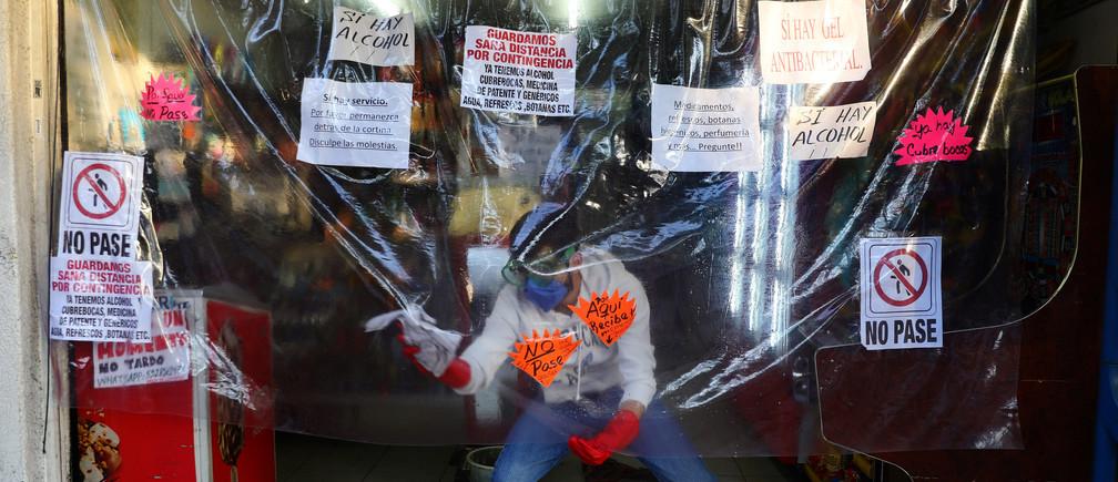 Un hombre limpia una lámina de plástico instalada como medida de protección en una tienda local, mientras continúa el brote de la enfermedad coronavirus (COVID-19), en Ciudad de México, México, el 3 de mayo de 2020.
