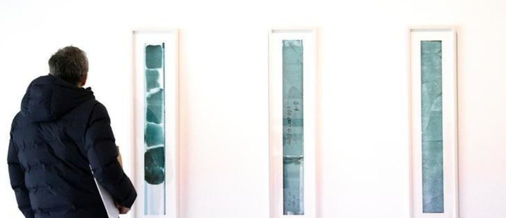 A man looks at a photo of ice cores drilled from the depths of the Greenland Ice Sheet, displayed as part of an installation called '88 Cores' by artist Peggy Weil at New York's Climate Museum inaugural show, featured at the Parson's School of Design in New York City, U.S., February 6, 2018. Picture taken February 6, 2018.  REUTERS/Brendan McDermid