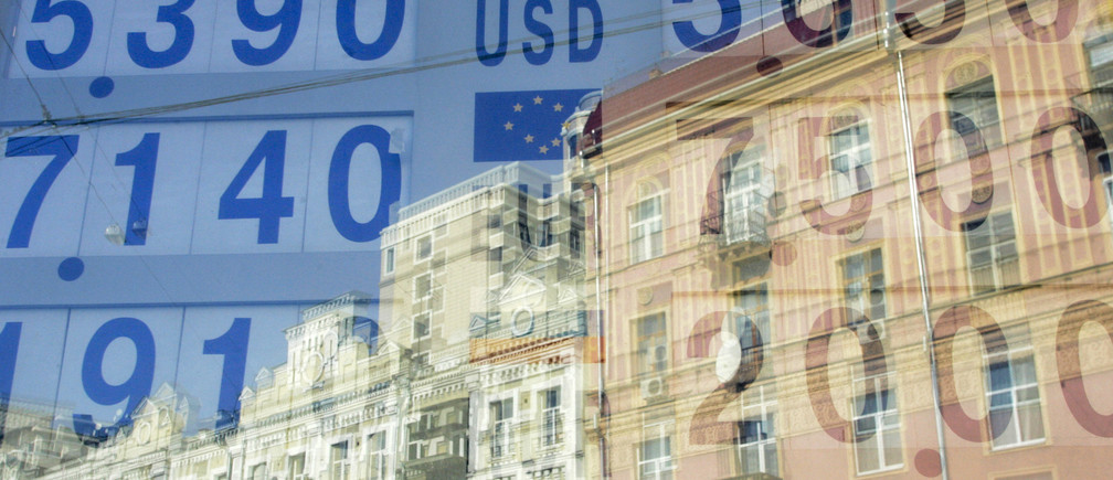 """Currency exchange rates are reflected in a window in Kiev October 22, 2008. Prime Minister Yulia Tymoshenko said on Wednesday she hoped Ukraine would receive """"substantial"""" international financial aid next week and set out measures aimed at shielding the country from what she called """"stagnation"""". REUTERS/Konstantin Chernichkin (UKRAINE) - GM1E4AM1OM501"""