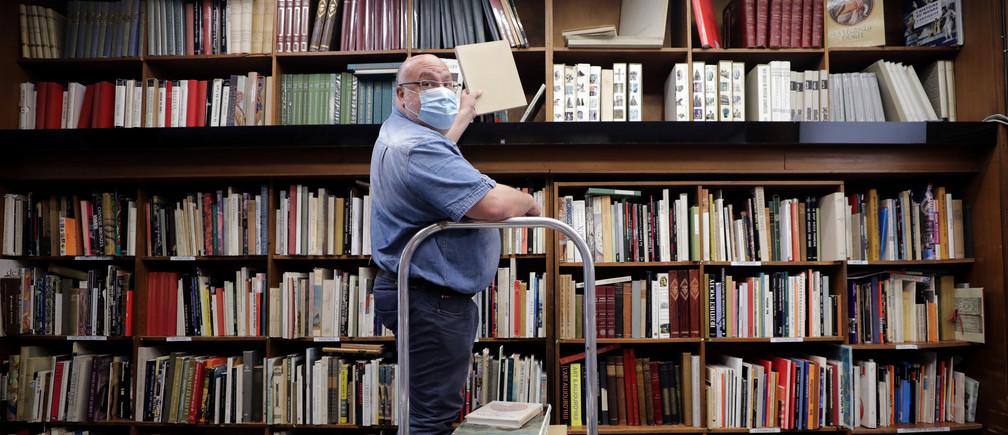 El librero Philippe Seyrat, con una máscara facial protectora, coloca libros en la librería La Sorbona de Niza mientras Francia suaviza sus estrictas reglas de cierre durante el brote de la enfermedad coronavirus (COVID-19) en Francia, el 13 de mayo de 2020.