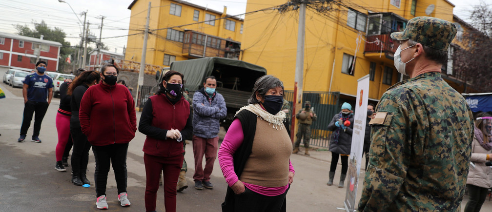 Locals line up to receive food from the army at a socially vulnerable community following the outbreak of the coronavirus disease (COVID-19) in Maipu area at Santiago, Chile June 16, 2020. REUTERS/Ivan Alvarado - RC2KAH9Y7HDZ