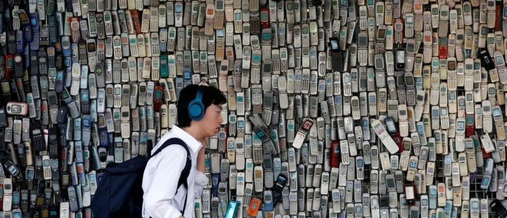 A man using a smartphone walks past an electronic shop's wall decorated with old cell phones which its owner Watanabe Masanao had collected over 20 years is pictured in Tokyo, Japan July 5, 2017. REUTERS/Kim Kyung-Hoon     TPX IMAGES OF THE DAY - RC15ACF4F070
