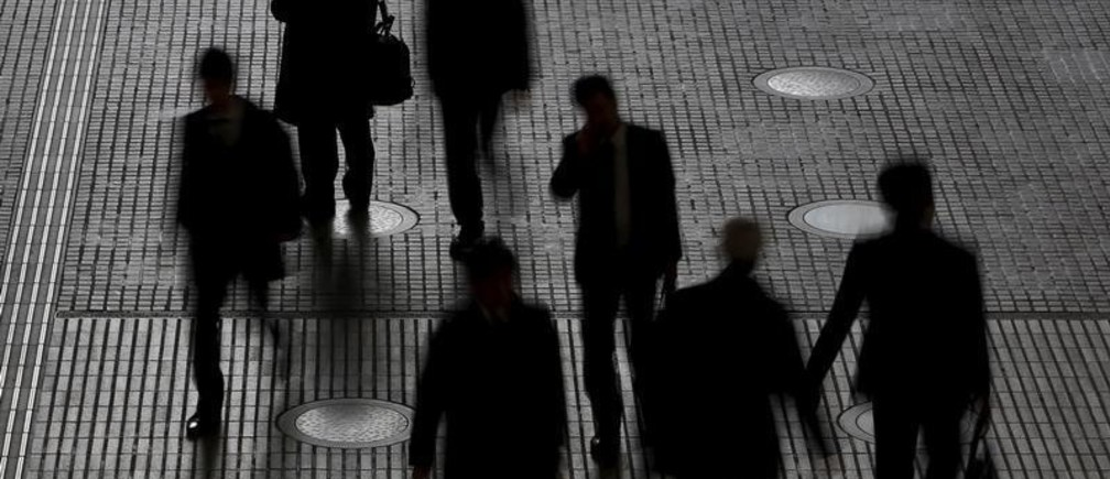 People walk at an office building at a business district in Tokyo, Japan, February 29, 2016. Japan's seasonally adjusted unemployment rate fell in January to 3.2 percent, data by the Ministry of Internal Affairs and Communications showed on Tuesday. Picture taken February 29, 2016.