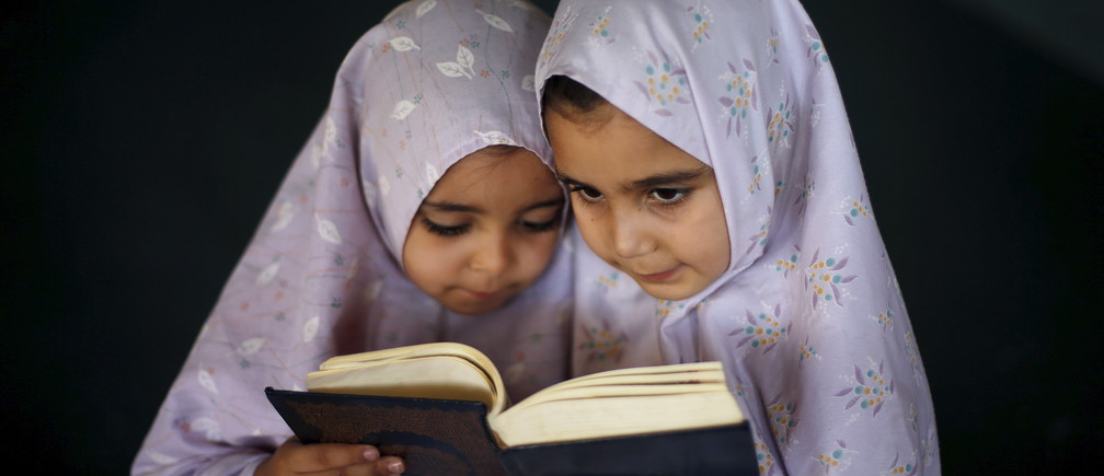 Palestinian girls read the Koran as they attend a Koran memorisation lesson during summer vacation inside a mosque in Gaza City June 7, 2015. REUTERS/Mohammed Salem      TPX IMAGES OF THE DAY      - RTX1FH1V