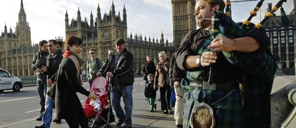 A busker plays bagpipes for tourists near the Houses of Parliament in London January 12, 2012.  A row between the British government in London and the SNP has escalated sharply in recent days, after British Prime Minister David Cameron on Sunday outlined a plan to bring forward the referendum, and restrict the questions asked.  Luke MacGregor  (BRITAIN - Tags: POLITICS CITYSPACE)