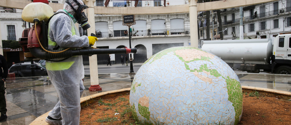 A worker wearing a protective suit disinfects a globe-shaped public garden, following the outbreak of coronavirus disease (COVID-19), in Algiers, Algeria March 23, 2020. REUTERS/Ramzi Boudina     TPX IMAGES OF THE DAY - RC2SPF9I75BS