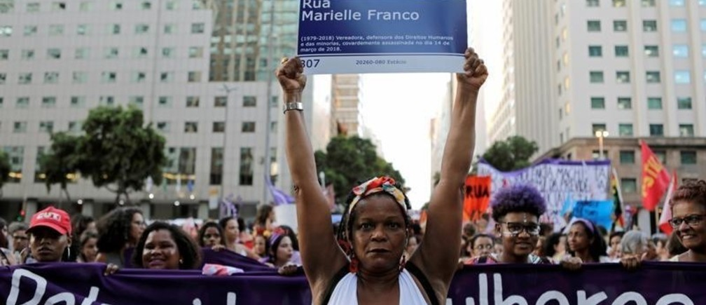 """A woman holds a street sign reading """"Street Marielle Franco"""", in tribute to late human rights activist and councilwoman Marielle Franco, who was assassinated in a shooting, as she participates in a rally during Women's Day celebrations in Rio de Janeiro, Brazil, March 8, 2019.     REUTERS/Sergio Moraes     TPX IMAGES OF THE DAY - RC1692124910"""