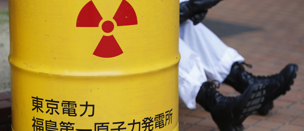 An anti-nuclear protester wearing a protective suit is seen behind a mock drum which is labelled as radioactive waste from Tokyo Electric Power Co's (TEPCO) Fukushima nuclear power plant, before he starts marching in Tokyo March 9, 2014. Thousands of protesters marched in the Japanese capital on Sunday, ahead of the third anniversary of an earthquake and tsunami that triggered the world's worst atomic disaster in 25 years. REUTERS/Yuya Shino (JAPAN - Tags: ANNIVERSARY DISASTER ENERGY CIVIL UNREST) - GM1EA391B1F01