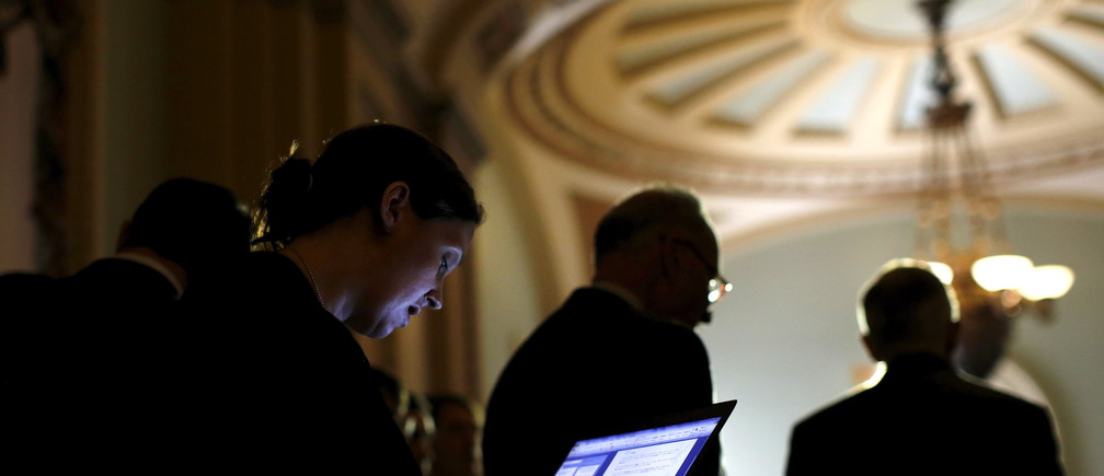 A journalist take notes on her laptop as U.S. Senate Minority Leader Harry Reid (D-NV) (R) talks to reporters during a new conference following party policy lunch meeting at the U.S. Capitol in Washington August 4, 2015. REUTERS/Carlos Barria - RTX1N22F