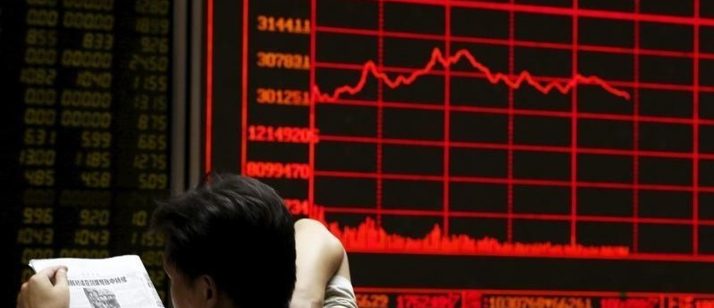 An investor reads a newspaper in front of an electronic board showing stock information at a brokerage house in Beijing, China, August 25, 2015.  China's major stock indexes sank more than 6 percent in early trade on Tuesday, after a catastrophic Monday that saw Chinese exchanges suffer their biggest losses since the global financial crisis, destabilising financial markets around the world.  REUTERS/Kim Kyung-Hoon - GF10000181773