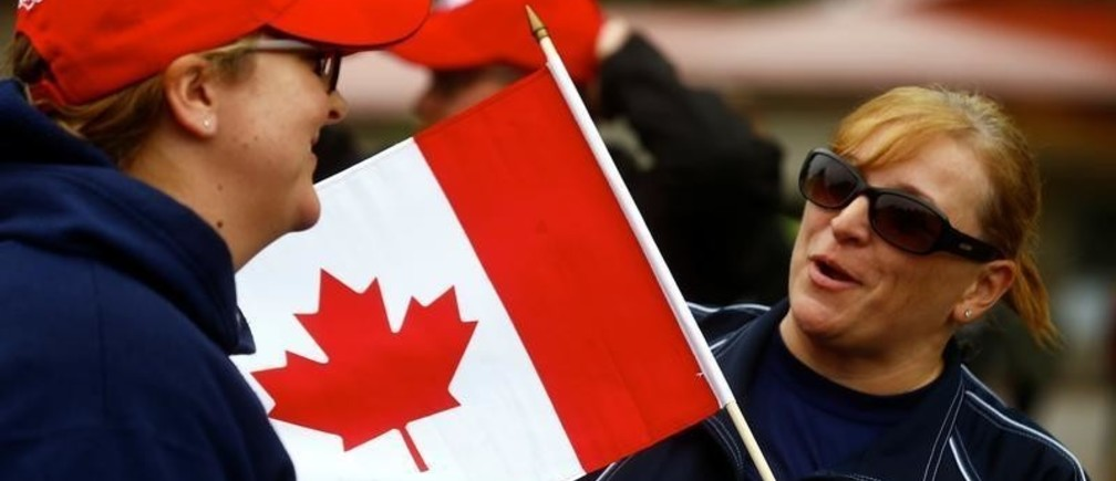 A woman holds a flag as Canadian-led NATO Enhanced Forward Presence battlegroup soldiers celebrate the 150th anniversary of the Confederation on Canada Day at Adazi Military Base, Latvia