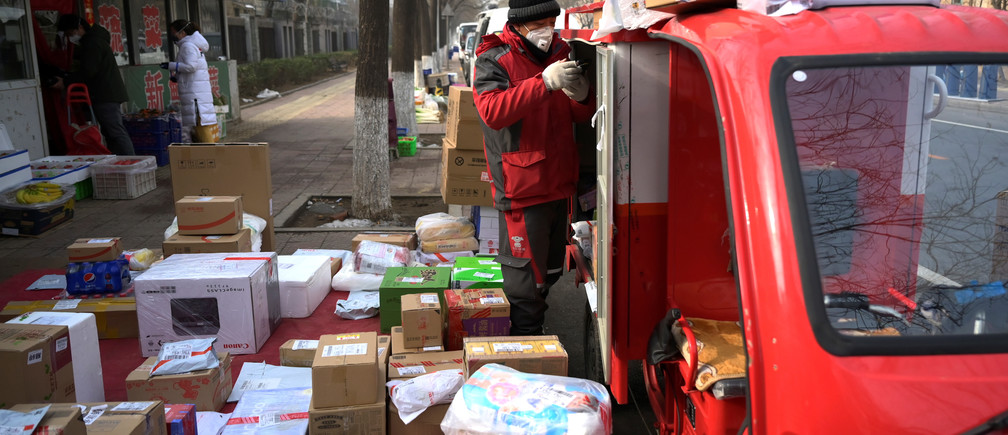 A JD.com delivery worker wearing a face mask unloads parcels outside a residential compound, as the country is hit by an outbreak of the novel coronavirus, in Beijing, China February 21, 2020. REUTERS/Tingshu Wang - RC2X4F99JTNL