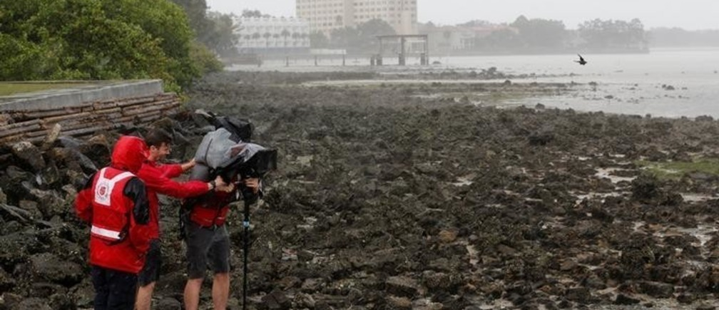 A video crew films Hillsborough Bay after water receded from the harbour ahead of the arrival of Hurricane Irma in Tampa, Florida, U.S., September 10, 2017. REUTERS/Chris Wattie