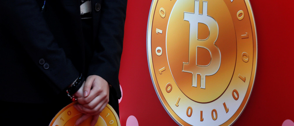 An attendant holds a bitcoin sign during the opening of Hong Kong's first bitcoin retail store February 28, 2014.