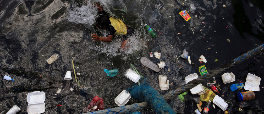 A boy swims in the polluted waters of the Manila bay to cool off from the intense heat within the slum area of the Baseco compound in Tondo, metro Manila, Philippines April 30, 2018. REUTERS/Romeo Ranoco - RC17978C2A20