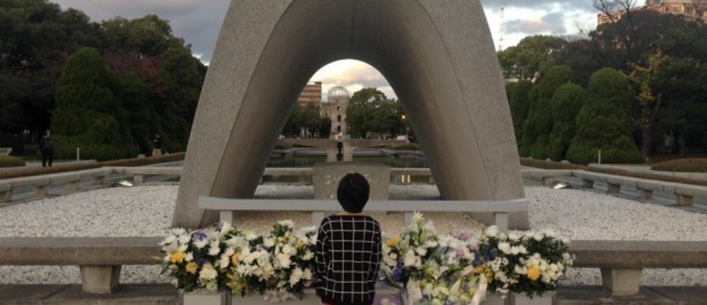 A child pays respect at the cenotaph at Hiroshima Peace Park