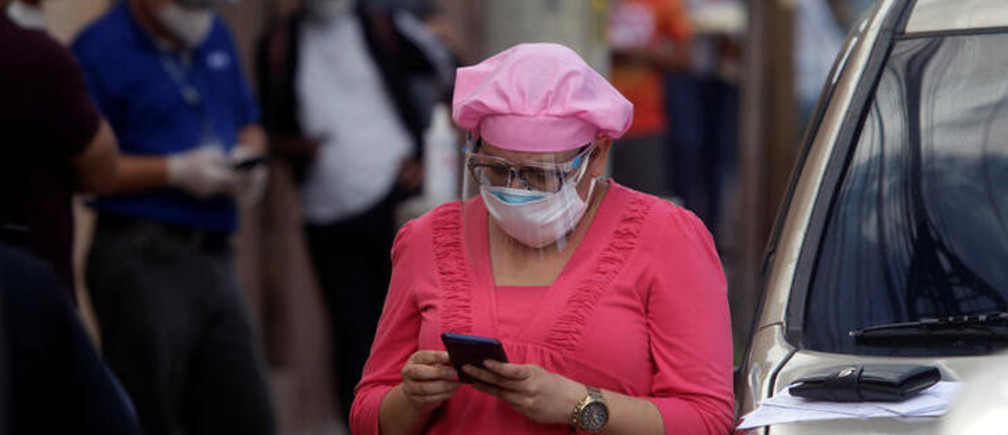 A woman checks her phone while waiting in line to be tested for the coronavirus disease (COVID-19), outside a private lab in Tegucigalpa, Honduras June 12, 2020. REUTERS/Jorge Cabrera