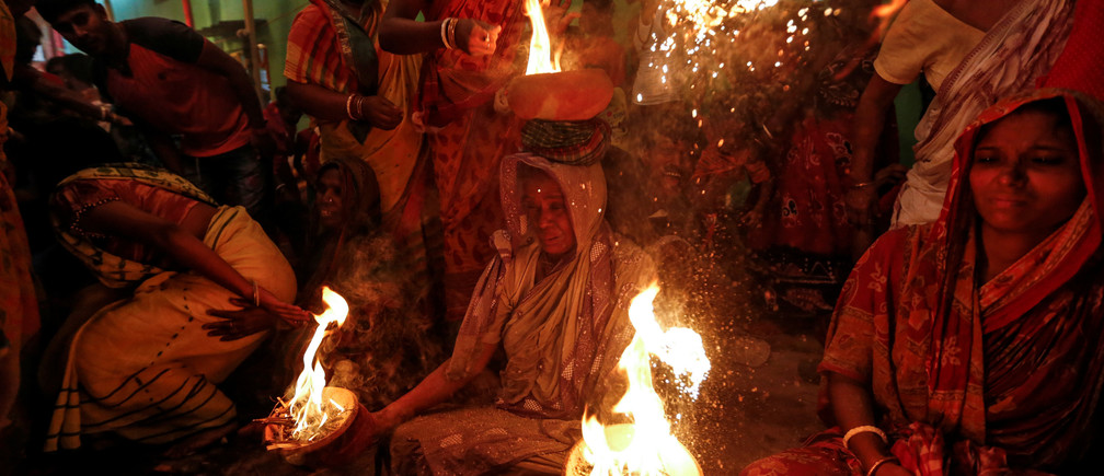 A woman holds earthen pots with fire during a ritual while worshipping Sheetala Mata, the Hindu goddess of smallpox, during Sheetala Puja in which devotees pray for the betterment of their family and society, in Kolkata, India, March 28, 2019. REUTERS/Rupak De Chowdhuri - RC187A814790