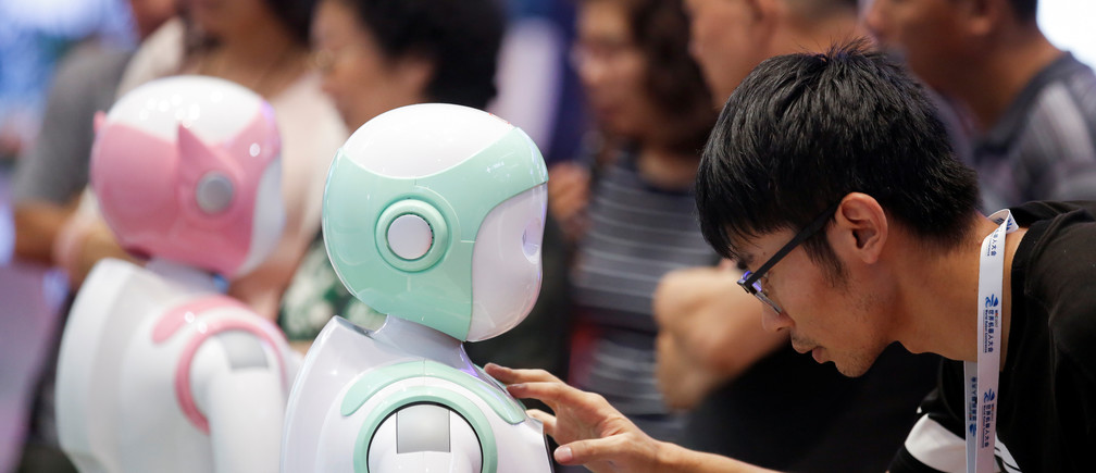 A man programs an iPal Companion Robot by Nanjing Avatar Mind Robot Technology at the 2017 World Robot conference in Beijing, China August 22, 2017.