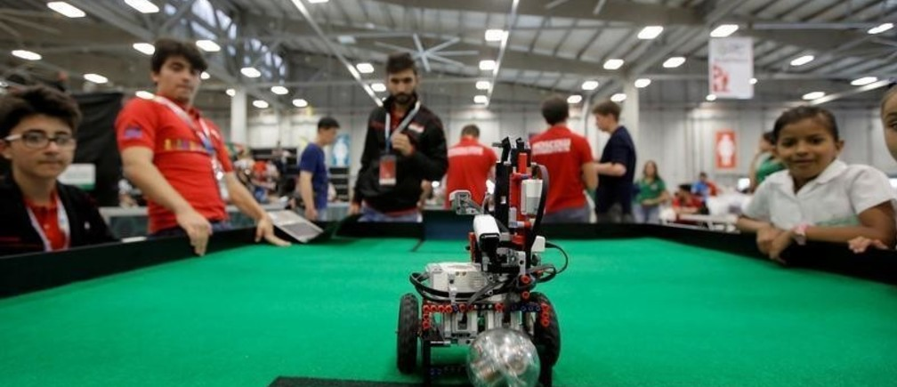 Miniature robots play soccer as participants look on during the World Robot Olympiad at a convention center in San Rafael de Alajuela, Costa Rica November 10, 2017. REUTERS/Juan Carlos Ulate - RC12C2CC65D0