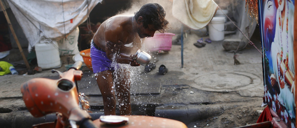 A migrant laborer bathes near a hotel construction site on a cold winter morning in New Delhi