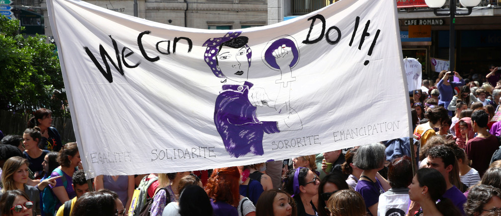 People hold a banner during a day-long and nationwide women's strike aimed at highlighting the country's poor record on defending the rights of women and families in Lausanne, Switzerland, June 14, 2019.  REUTERS/Denis Balibouse - RC1700A6F0B0