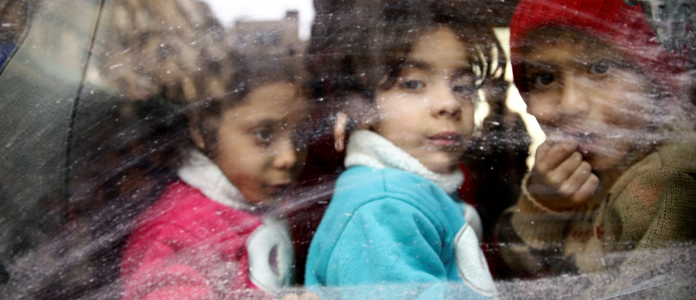 Children look through a bus window during evacuation from the besieged town of Douma, Eastern Ghouta, in Damascus, Syria March 13, 2018. REUTERS/Bassam Khabieh     TPX IMAGES OF THE DAY - RC1A80480B00