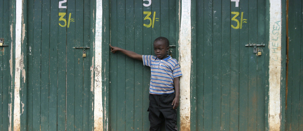 A boy stands at a public toilet at Kibera slum in Kenya's capital Nairobi August 15, 2008. Many such local facilities have been provided by aid organizations working to improve the living conditions in poor areas. REUTERS/Noor Khamis (KENYA) - RTR215Z0