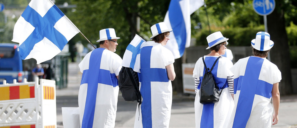 Finnish fans dress in their national colours and hold Finnish flags at the European Athletics Championships in Helsinki June 30, 2012. REUTERS/Yves Herman (FINLAND  - Tags: SPORT ATHLETICS)   - TB3E86U0WL9PF