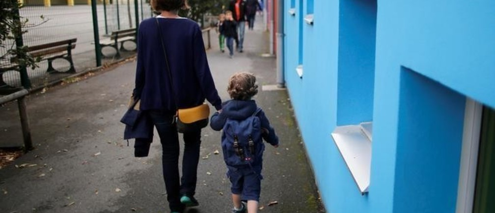 A mother and her son walk to arrive at the nursery school on the first day of the new school year in Vertou, France, September 4, 2017. REUTERS/Stephane Mahe
