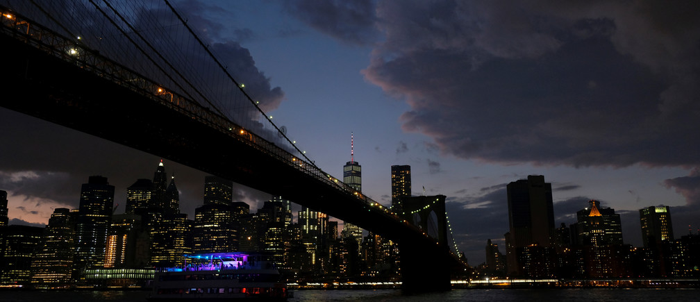 A ferry boat passes under Brooklyn Bridge in front of the night skyline of Lower Manhattan in New York City, U.S., at dusk, September 15, 2017. REUTERS/Darrin Zammit Lupi - RC1252C64BA0