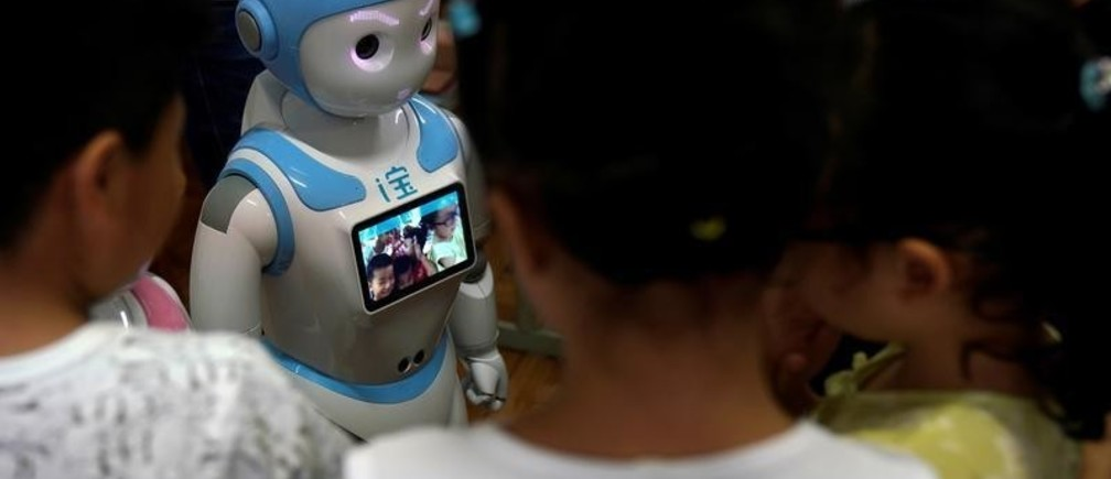 An iPal social robot, takes photographs of children at a kindergarten in Suzhou, Jiangsu province, China July 4, 2018. Designed to offer education, care and companionship to children and the elderly, the 3.5-feet tall humanoid robots come in two genders and can tell stories, take photos and deliver educational or promotional content. Picture taken July 4, 2018. REUTERS/Aly Song - RC1FBBBAEDD0