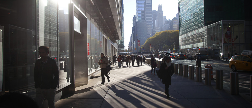 Commuters cast long shadows as they make their way through Times Square on a breezy and chilly fall morning in New York, November 18, 2014.  REUTERS/Carlo Allegri (UNITED STATES - Tags: SOCIETY ENVIRONMENT) - GM1EABJ01YB01
