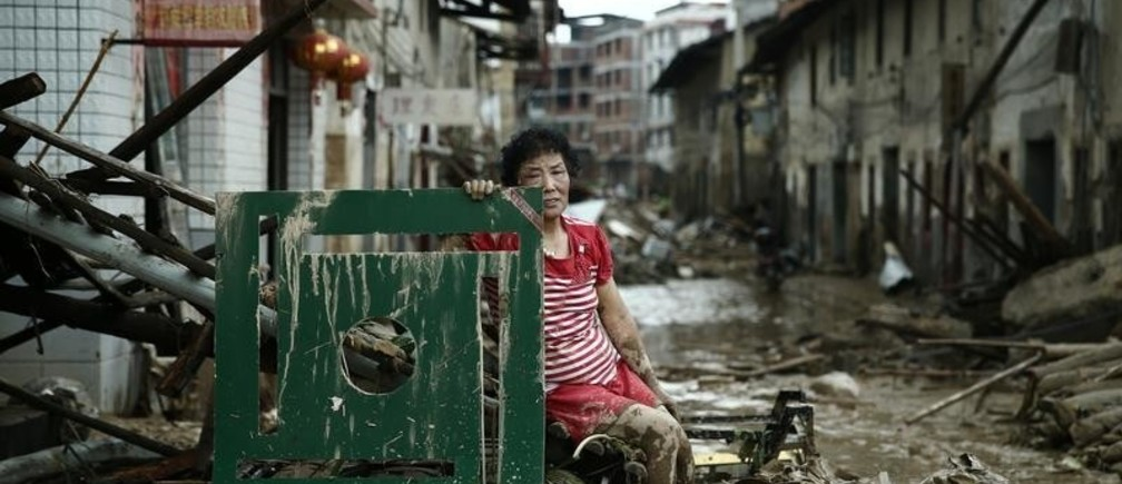 A woman sits on the ruins after typhoon Nepartak swept through Minqing county, Fujian province, China, July 10, 2016. Picture taken July 10, 2016. REUTERS/Stringer REUTERS ATTENTION EDITORS - THIS IMAGE WAS PROVIDED BY A THIRD PARTY. EDITORIAL USE ONLY. CHINA OUT. NO COMMERCIAL OR EDITORIAL SALES IN CHINA.      TPX IMAGES OF THE DAY      - S1AETOXMOIAA