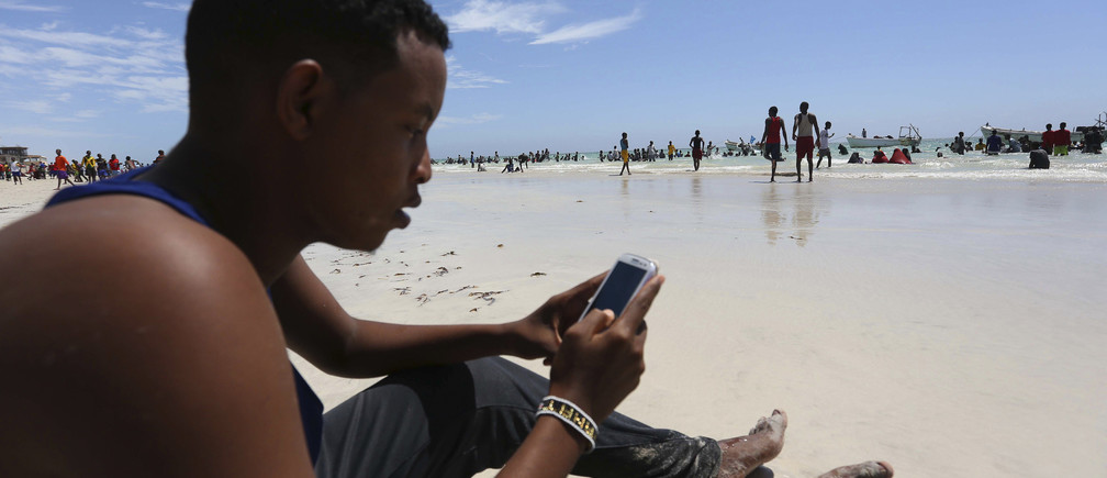 """A Somali man browses the internet on his mobile phone at a beach along the Indian Ocean coastline in Somalia's capital Mogadishu, January 10, 2014. Somali rebel group al Shabaab has banned the use of the Internet in the Horn of Africa country, giving telecom operators 15 days to comply with the order, the militants said. """"Any company or person who fails to comply with the rule will be dealt with according to the Islamic sharia,"""" the group said in a statement posted on the Internet."""