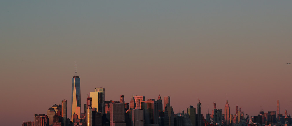 The setting sun is seen reflecting off 1 World Trade Center and other buildings in Manhattan in New York City, U.S., December 4, 2018. REUTERS/Brendan McDermid - RC1C0DDF16A0